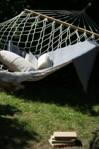 Hammock in the garden with books, pillow and blanket