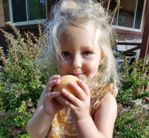 Sweet little peach Andie gets ready to sample a Palisade peach!